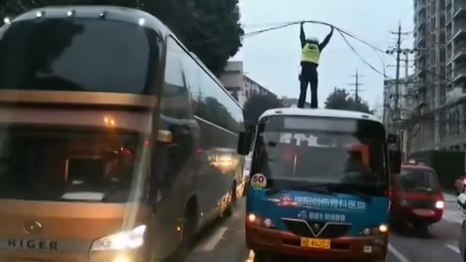光缆垂落致交通受阻,绵阳交警站公交车顶托举20分钟
