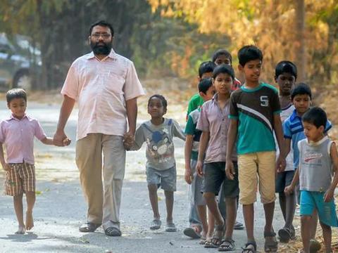 印度一男子不顾家人反对,收养16个患病孤儿,并同吃同住!