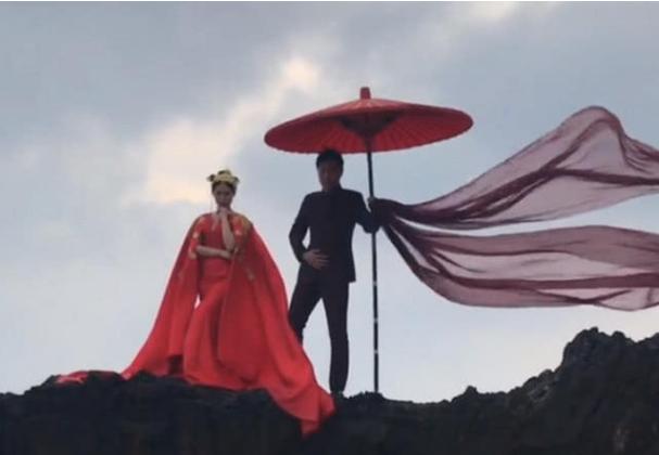 夫妻海边拍婚纱照,特大红伞做道具,网友:成片像法海守护白素贞