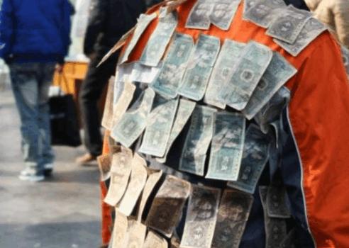 男子身上贴着旧纸币引人围观,得知男子用意后,众人点赞