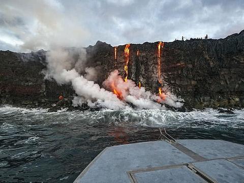 火山喷发温度高达870度,岩浆奔腾男子赤膊站立一旁无惧色