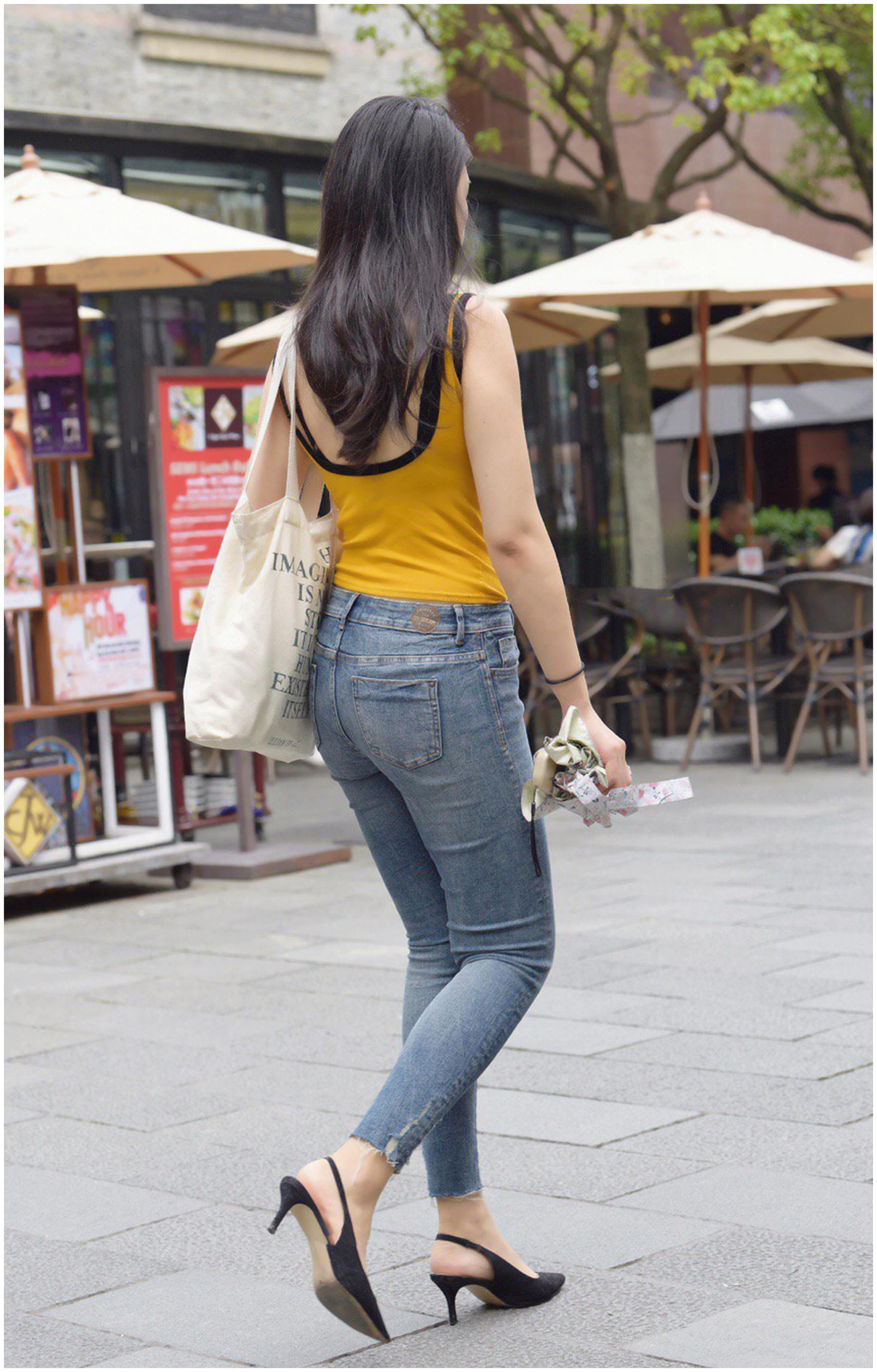 紧身牛仔裤_时尚街拍:蓝色紧身牛仔裤搭配黄色无袖背心,小姐姐很有活力