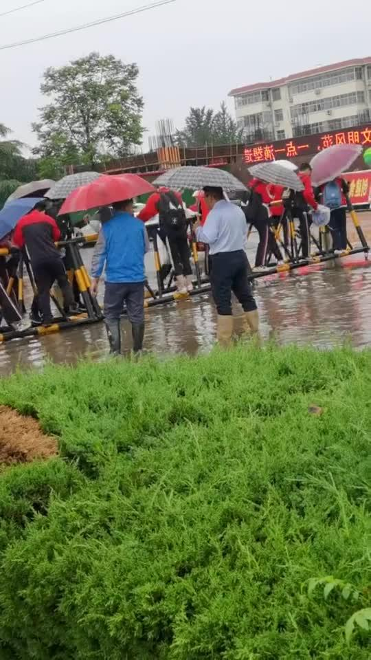 暴雨过后学校积水猛涨,老师们为学生搭建独木桥,在道路上...