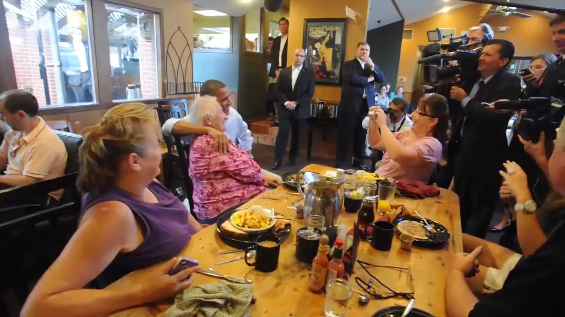 奥巴马总统在餐厅里,听到老太太想合影,急忙半跪着实现她的愿望