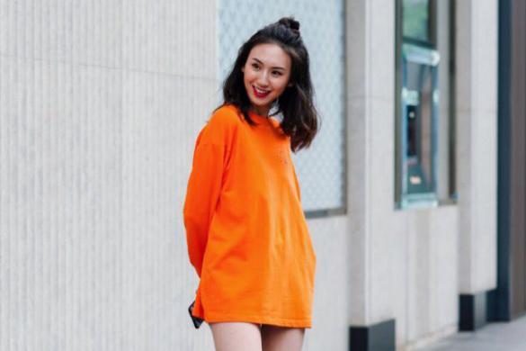 身穿橙色卫衣的女生,漏出又白又细的大长腿,靓丽逼人