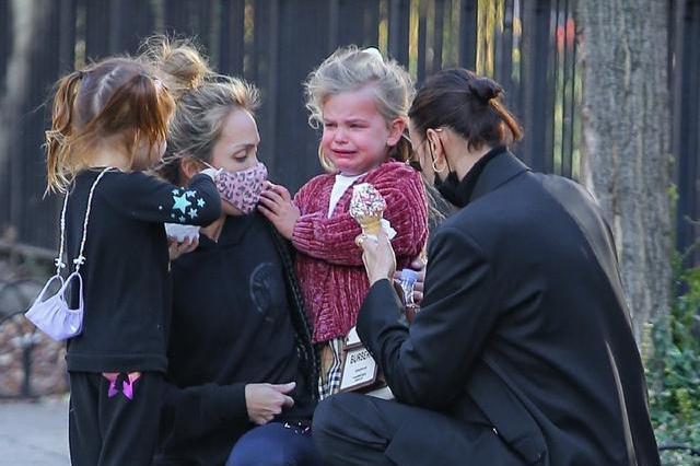 伊莉娜·莎伊克穿一身黑色西装带娃时尚干练,女儿像个小公主!