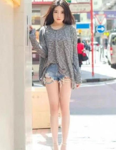 街拍:夸张的蝙蝠露背衫搭配毛边牛仔短裤 休闲时尚