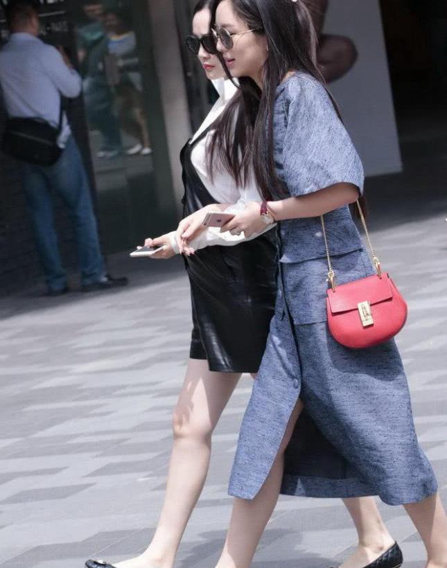 街拍:时髦的一对姐妹花 穿衣风格即为相似 戴黑墨镜有点酷