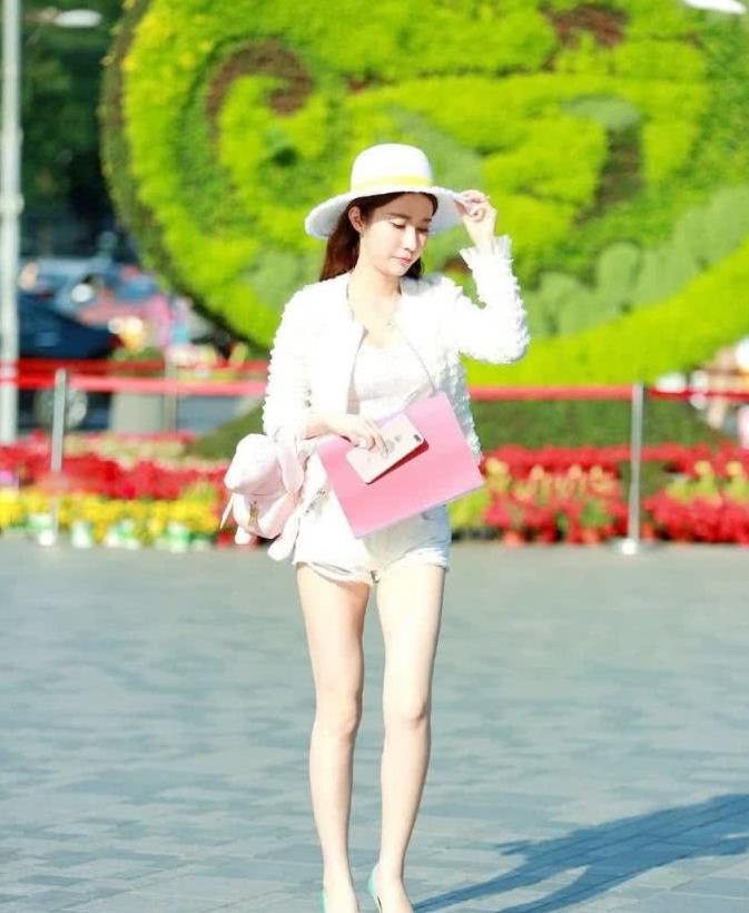 街拍:小姐姐身穿白色套装,头戴白色圆帽很有女神气质