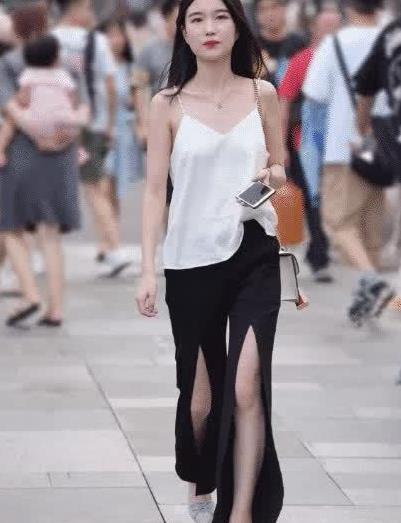 白色的吊带上衣,搭配的是一条黑色的长筒裤子,有点非主流