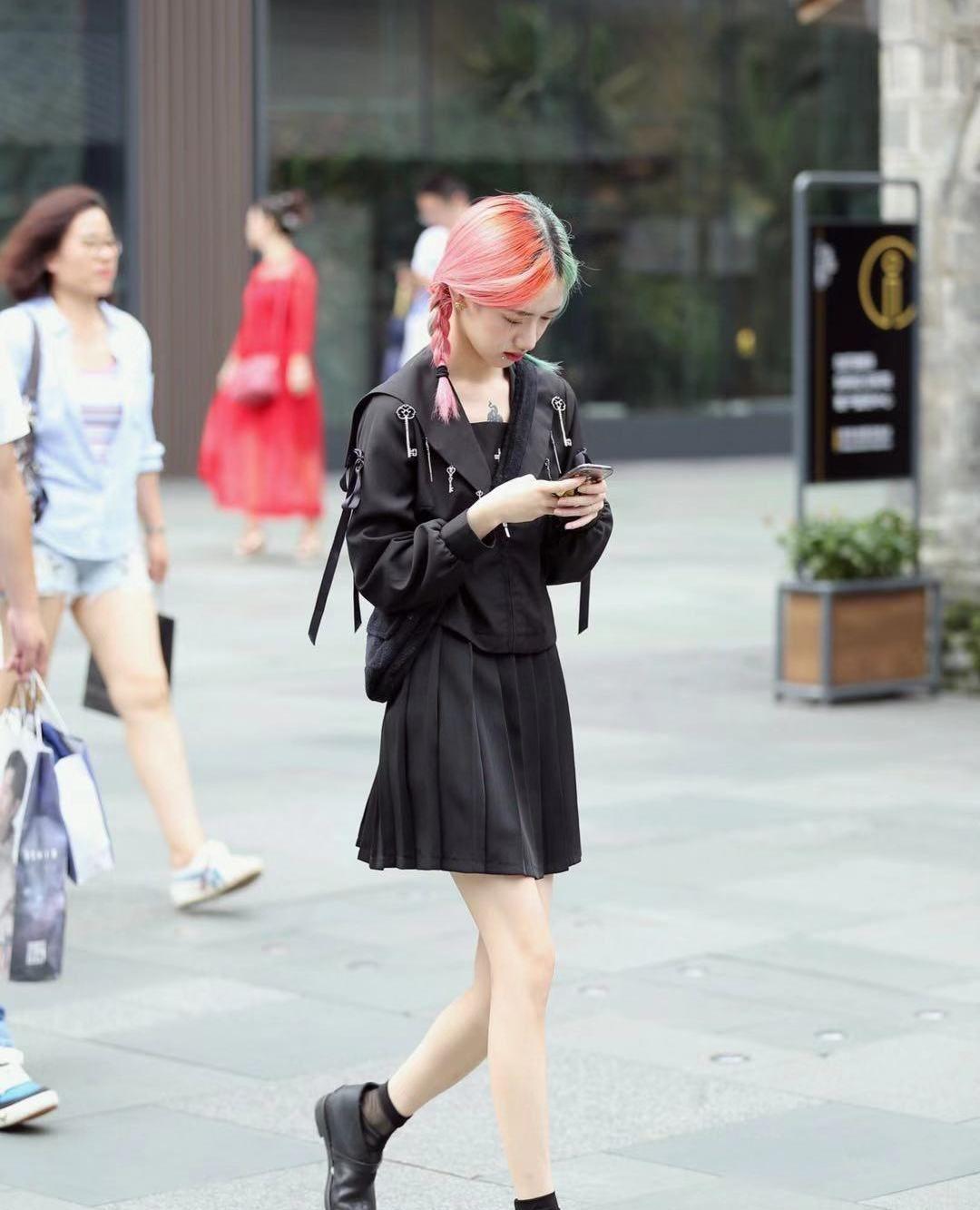 街拍,小姐姐黑色上衣搭配同色百褶裙,麻花辫清纯甜美发色吸睛