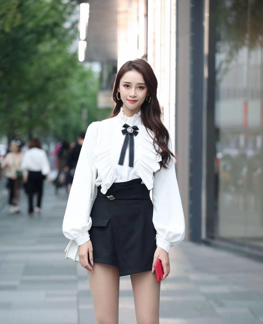 街拍,小姐姐白色荷叶边衬衫搭配黑色短裙,长发披肩笑容甜美