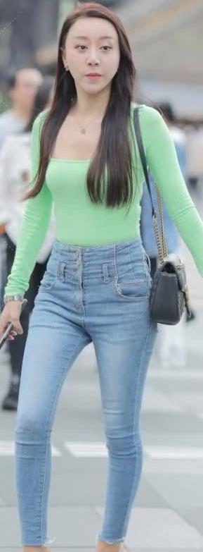 街拍:小姐姐上身绿色针织长T搭搭牛仔裤,青春靓丽