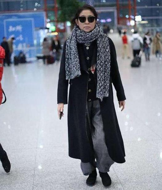 倪萍平时还真会赶时髦,一身潮姐的打扮,机场现身好似置身秀场
