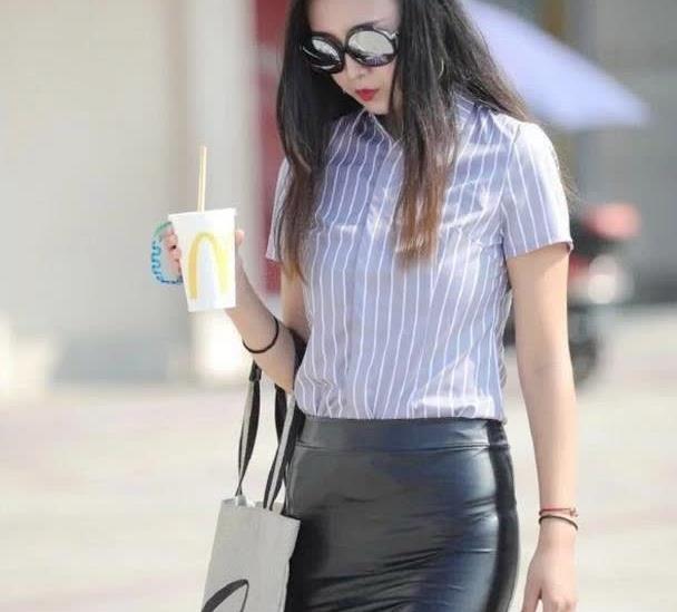 浅紫色竖条纹短袖衬衫,搭配紧身黑色皮裙,火爆又热辣