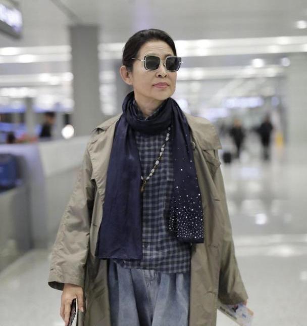 倪萍瘦身后终于时尚了,穿风衣配萝卜裤走机场,方形墨镜好洋气