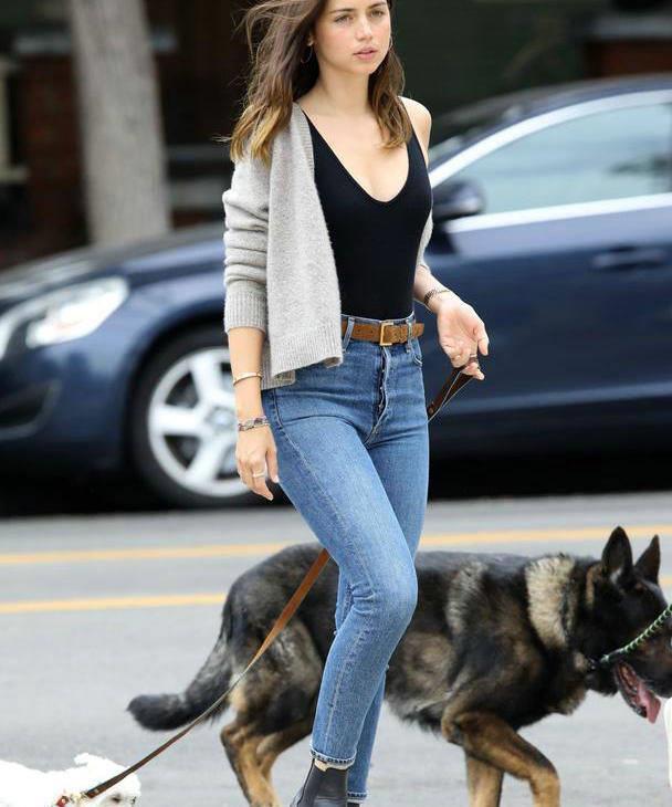 安娜·德·阿玛斯穿黑色上衣搭牛仔裤显休闲,遛狗散步轻松惬意