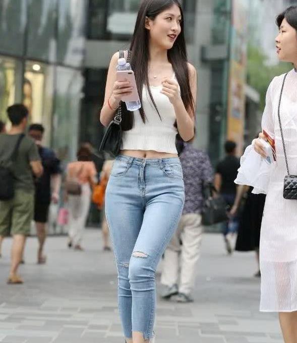 街拍:小姐姐身穿高腰牛仔裤,充满年轻人时尚的气息