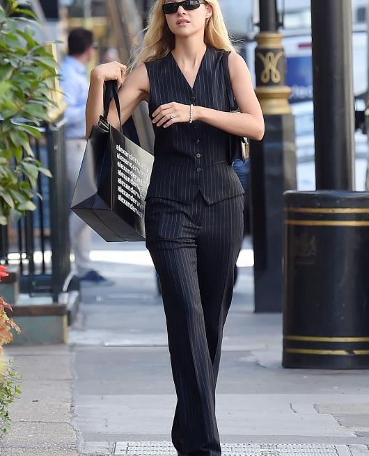 妮可拉·佩尔茨穿黑色套装亮相街头,墨镜增高鞋时尚魅力足