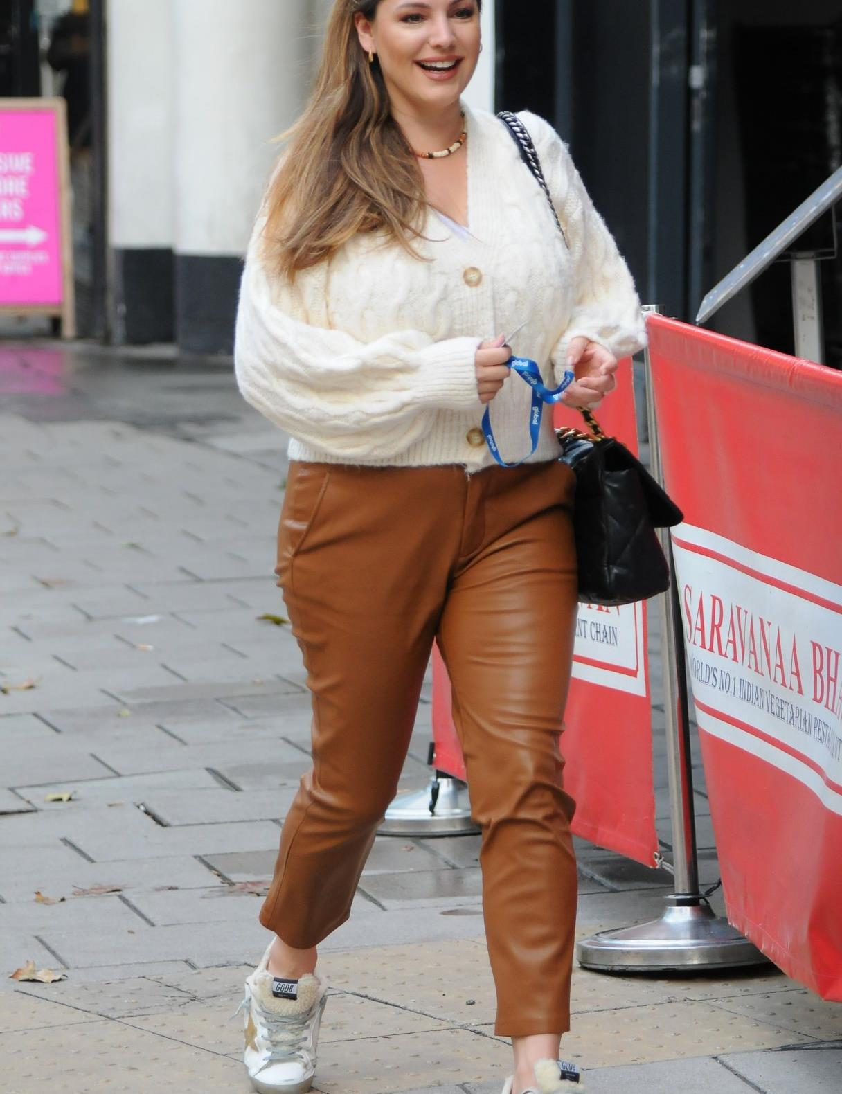 凯莉·布鲁克穿白色长袖上衣搭棕色长裤时髦靓丽,甜笑挥手气质佳