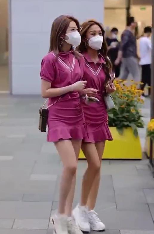 街拍:双胞胎粉衣同款衣裙小姐妹俩 白球鞋手挽着手背着LV精美包