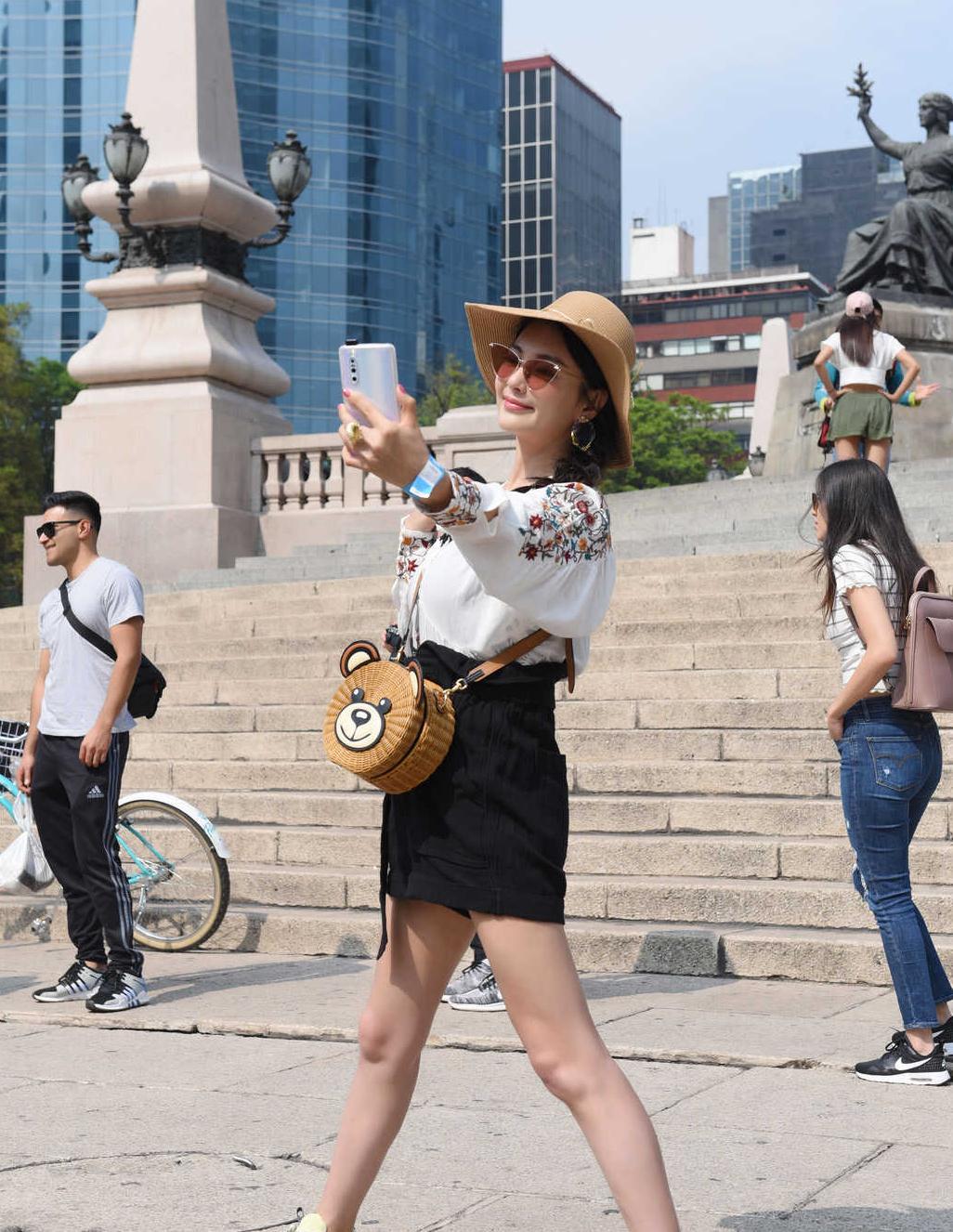 张雨绮国外度假真洋气,穿印花衬衫配高腰短裤,熊仔包太可爱了
