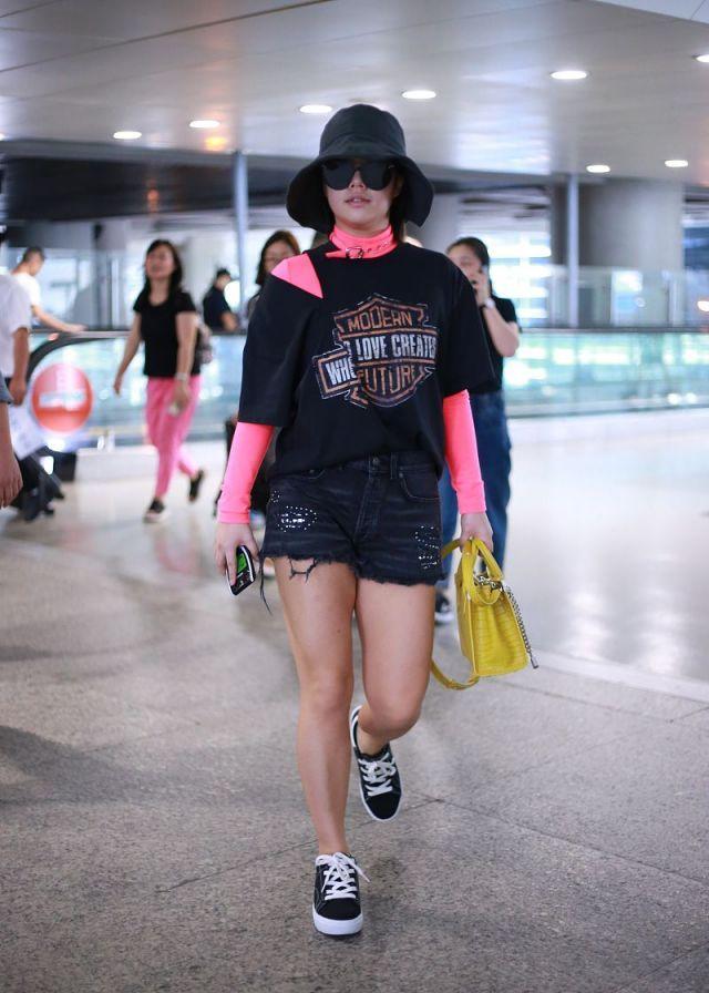 王菊现身机场穿热裤秀长腿,小麦色皮肤超健美