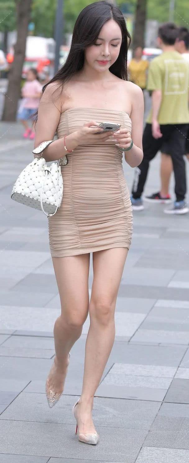 街拍美女:肤白貌美的紧身裙美女,一头长发显得她时尚前卫