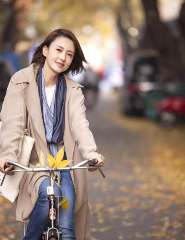 张蕾私服真显气质!浅棕风衣配牛仔裤气质高级,骑自行车拍唯美照
