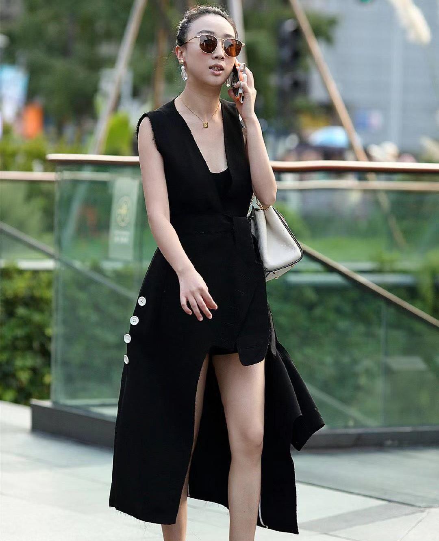 街拍:小姐姐一身黑色无袖不规则长裙,时尚大方丸子头清爽利落