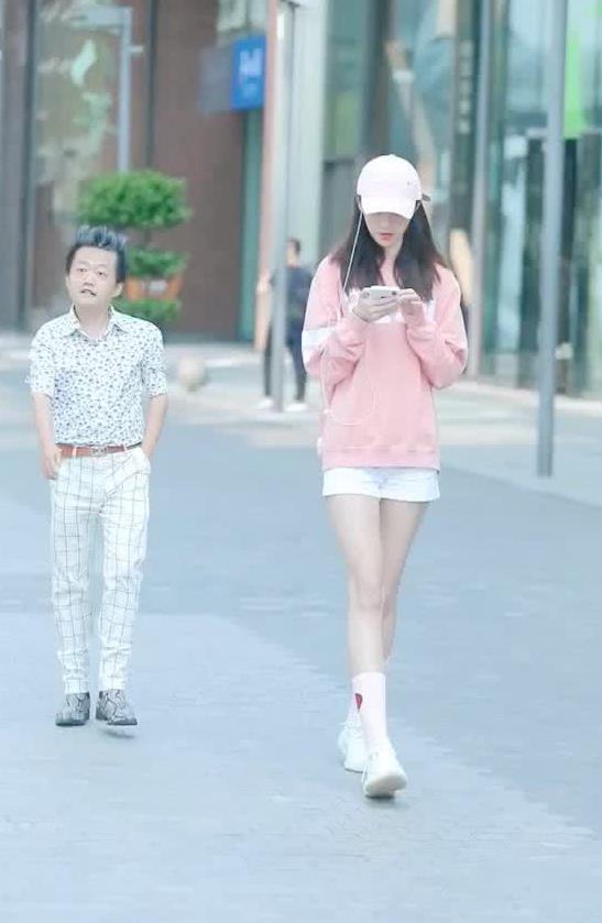 街拍:小姐姐身穿粉色卫衣搭白色短裤,尽显高挑身材