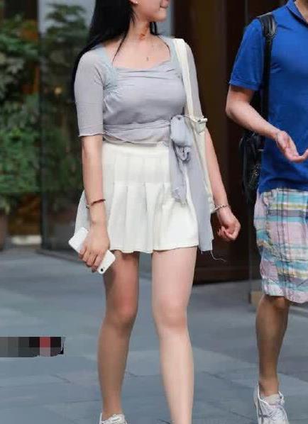 街拍:美女百褶裙搭白色运动鞋,青春靓丽突显迷人气质