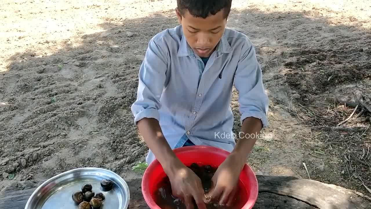 黝黑厨师村外烹饪,中午吃田螺肉,清洗干净一锅煮,鲜嫩可口
