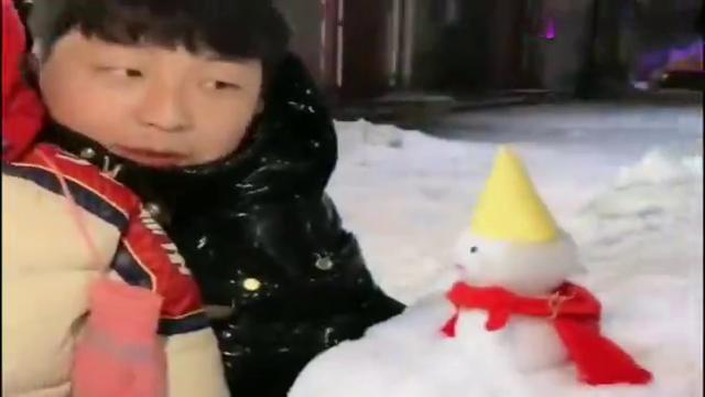 爸爸给暖宝堆了一个小雪人,暖宝看到后嫌弃它太小了