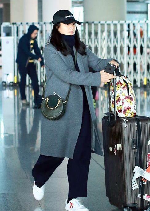 朱丹穿灰色大衣配鸭舌帽现身机场,素颜脸庞更大与路人并无二致