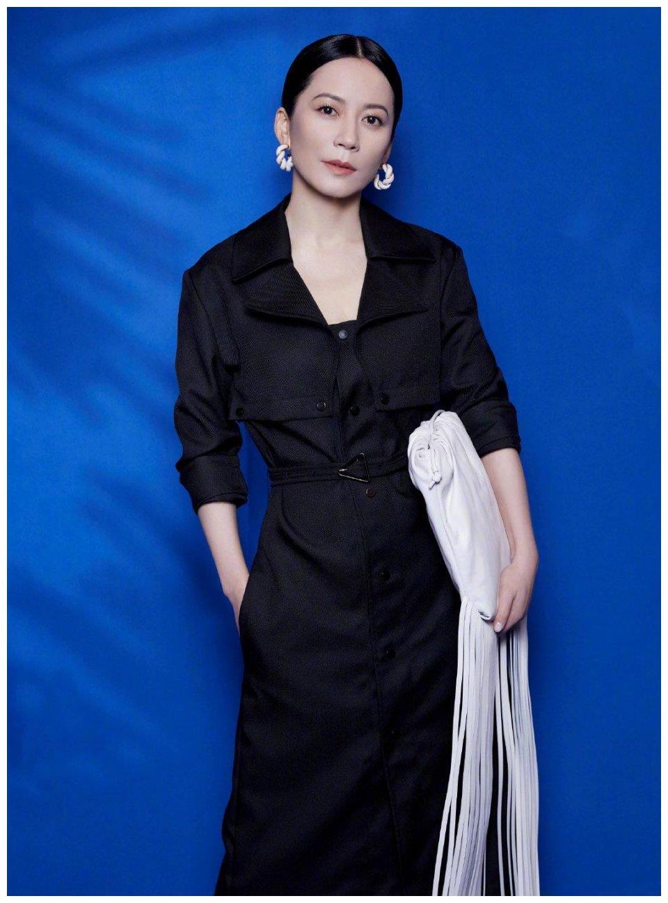 不老女神俞飞鸿真会搭,黑色风衣裙配白色流苏包,时尚里透着高级
