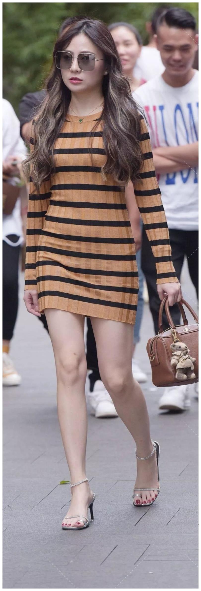 美女穿着横条纹的连衣裙,看上去非常的优雅迷人,很是养眼
