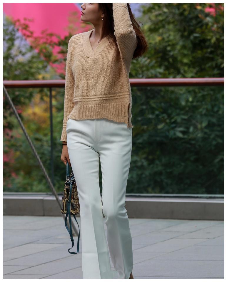 米色宽松毛衣,搭配白色西装裤,举止优雅,气质出众