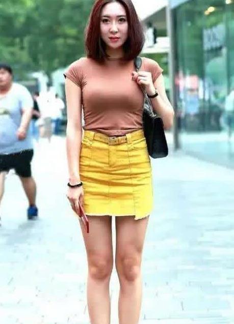 街拍美女,一条橙色包臀裙撑起了时尚的美