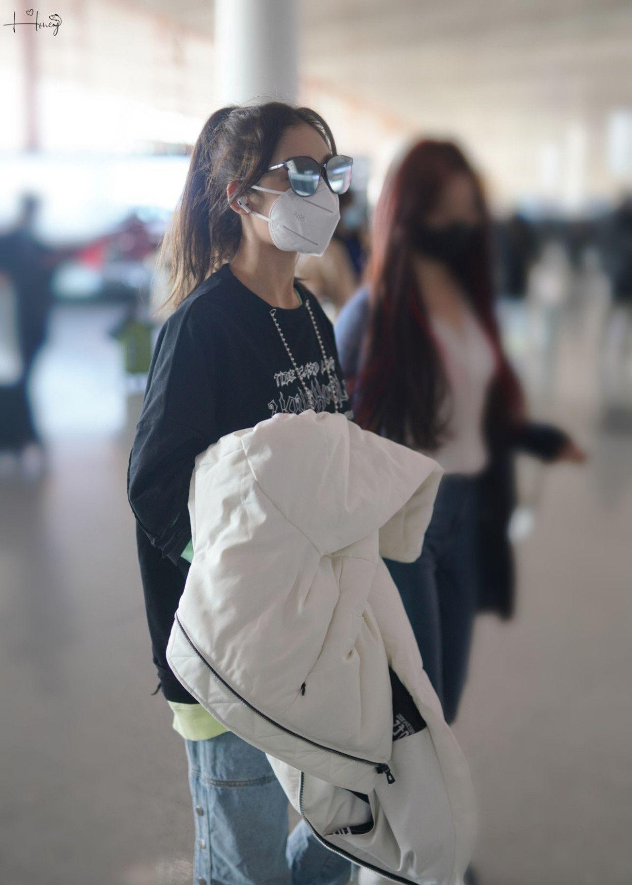 希林娜依高机场街拍,身穿纽扣牛仔裤和毛边帆布鞋,玩转街头潮流