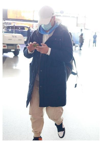 林峰双手插兜现身机场 边走边玩手机变身网瘾大叔