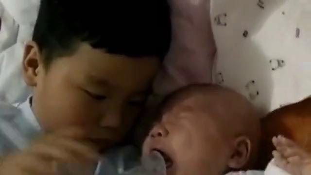 小弟弟一直在哭,哥哥很有耐心地喂弟弟奶嘴,这一幕好暖心啊!