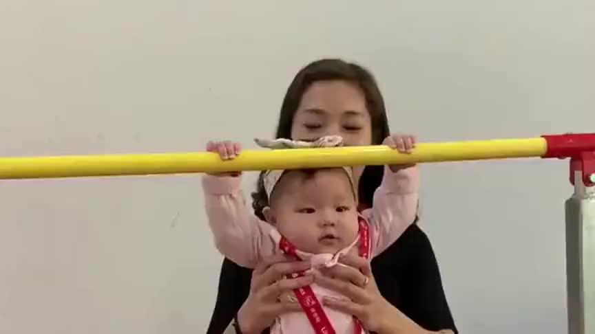 这个小宝宝太厉害了,小小年纪就可以抓单杠,这臂力可以!