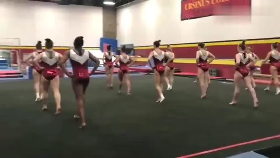 美国大学体操训练现场,姑娘完成一套高难度动作,与队友开心庆祝