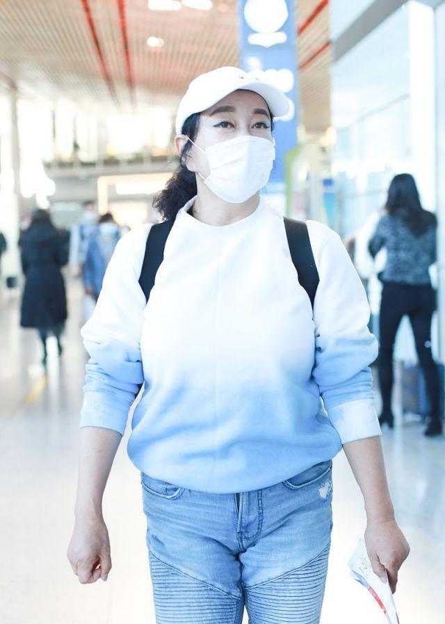 刘晓庆小跑赶飞机不忘挥手道别风风火火,穿长款羽绒服造型时髦