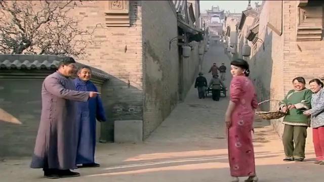 美女穿着高跟鞋跟旗袍,被村里人笑着