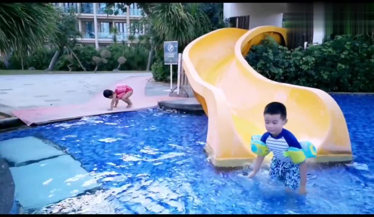 妈妈陪女儿在游泳池里玩水上滑滑梯,真好玩,美好的亲子时光