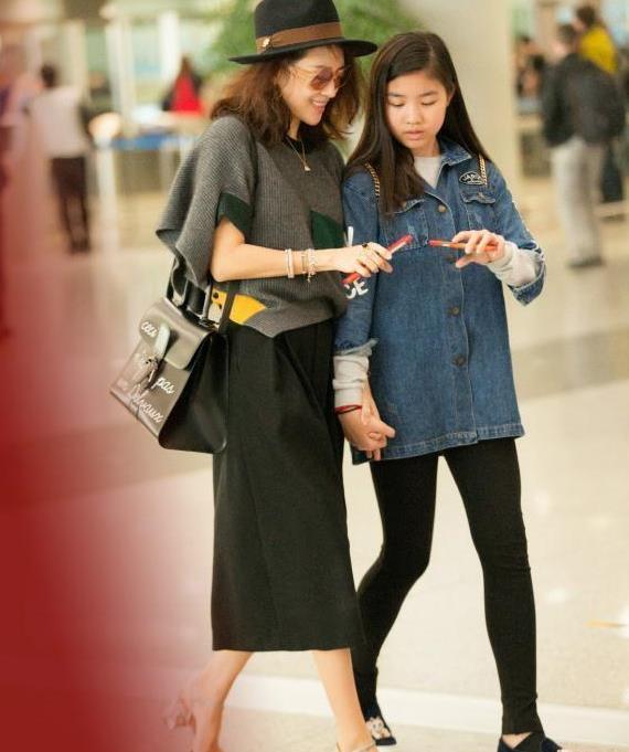 章子怡携继女走机场,穿纯色素装显大气,小苹果身高接近170