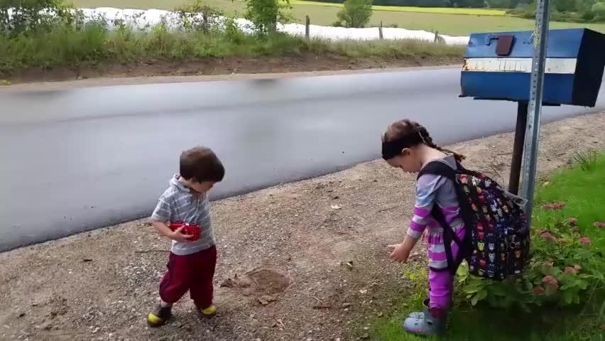 弟弟陪姐姐等校车,姐姐全程看护弟弟不让去危险地方,太有爱了