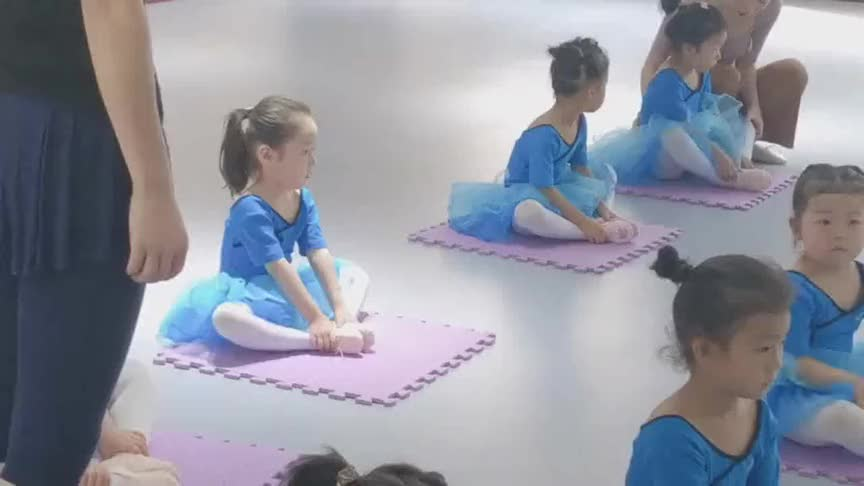 舞蹈课上看见妈妈在外面拿手机拍她,小姑娘立马坐正,太有镜头感